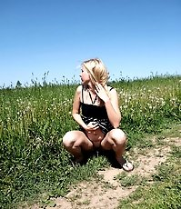 Super-beautiful blond girl piddling on a meadow