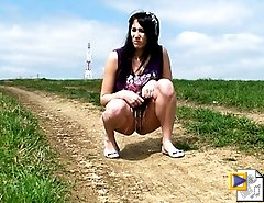 Brunette ho peeing in the middle of a country road