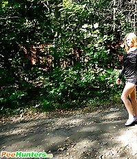 Naughty blonde girl takes a leak in the woods