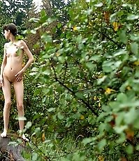Slim teenage nudist chick caught peeing in bush