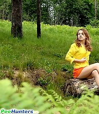 Kinky beauty makes piddle while sitting on a log