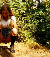 Leggy blonde girl empties her bladder under a tree