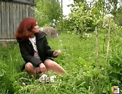 Redhair girl pissing near the road