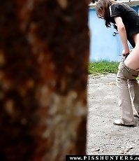 Sweet young beauty squats to have a leak in a yard
