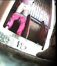 Two girls watering the spy cam planted in park loo