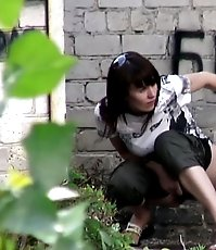 Amazing brunette caught doing a pee behind a building